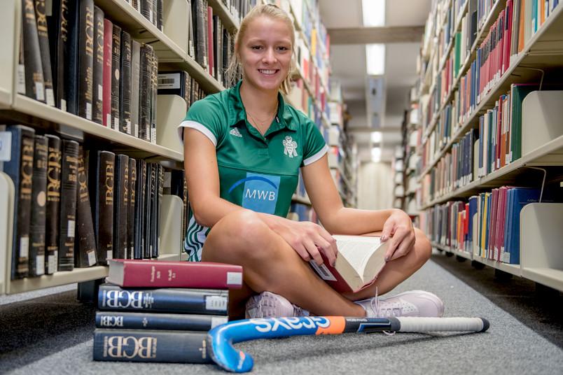 Hockeyspielerin im Trikot in der Unibibliothek