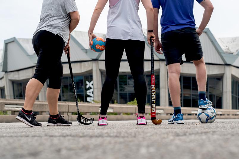 Drei Sportlerinnen und Sportler von hinten, mit diversen Sportgeräten