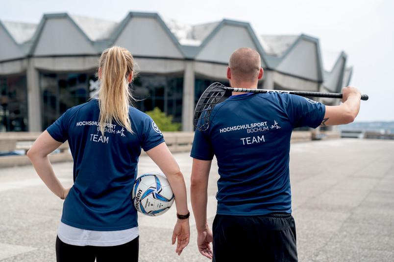Eine Frau mit Fußball unter dem Arm und ein Mann mit Hockeyschläger über der Schulter von hinten