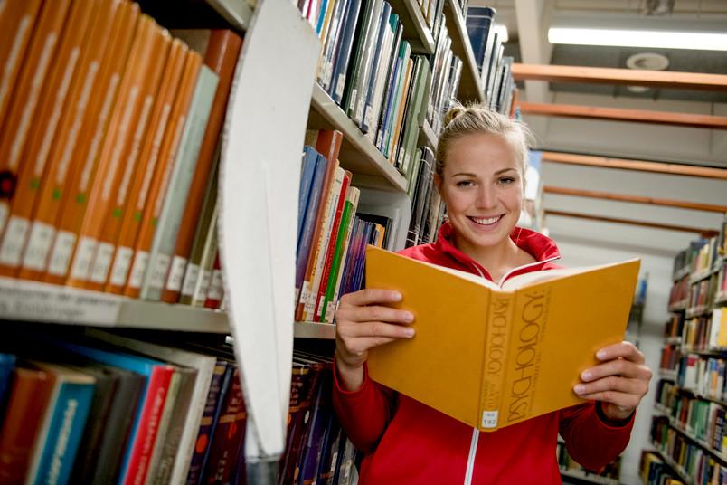 Eine Frau und ein Ruder lehnen an einem Bücherregal. Sie hat ein Buch geöffnet und lacht.