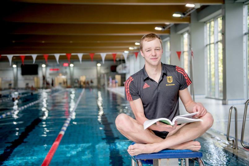 Student sitzt am Schwimmbecken.