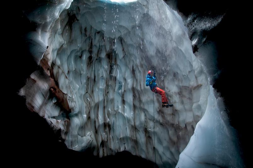 Ein Mann seilt sich in eine Eishöhle ab.