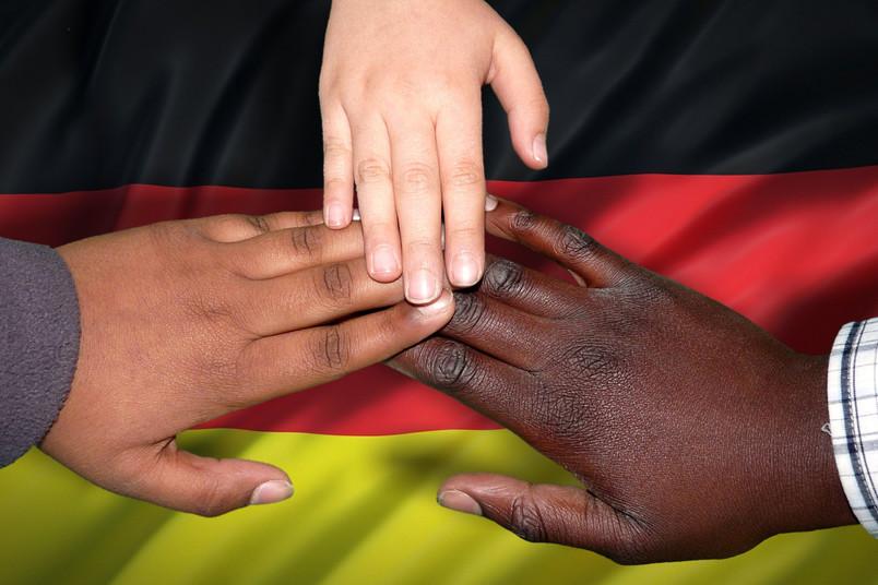 Integration: Drei verschieden farbige Hände liegen auf der Deutschlandflagge