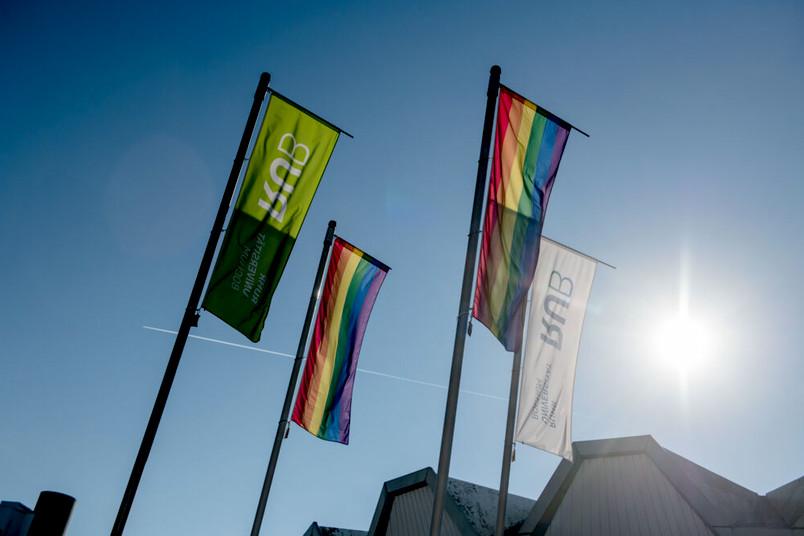 Vier Flaggen vor strahlend blauem Himmel. Zwei der Flaggen sind in Regenbogenfarben gestreift. Im Hintergrund ist ein Stück des Audimax zu sehen.
