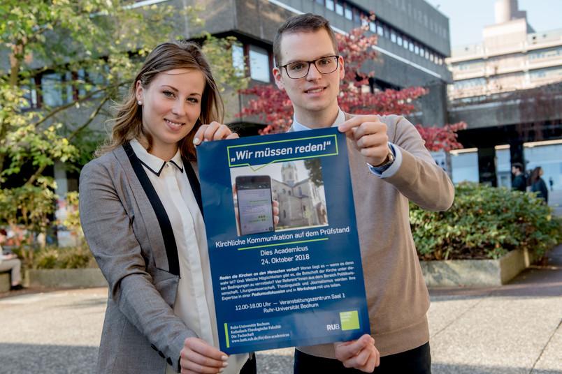 Zwei Studierende halten Poster in Kamera.