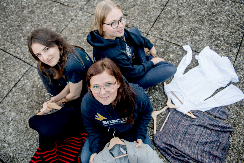Drei Studentinnen sitzen auf dem Boden.
