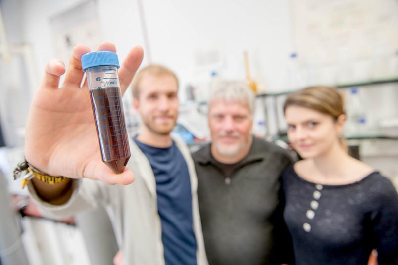 Forscher halten ein Reagenzglas mit dunkler Flüssigkeit in die Kamera.