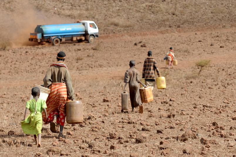 <div> Menschen in der Nähe einer Wasserstelle in Kenia, die mit frischem Trinkwasser aus einem Tankfahrzeug versorgt werden sollen</div>