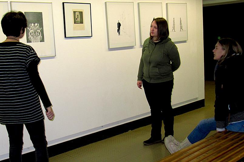 Objekte einer Kunstausstellung werden betrachtet