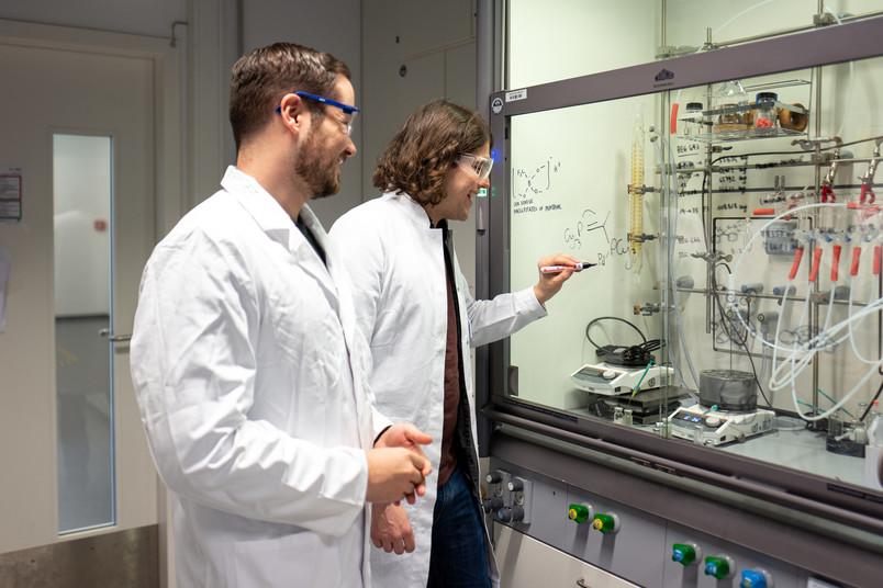 Zwei Forscher in Kitteln schreiben chemische Formeln an eine Glasscheibe.