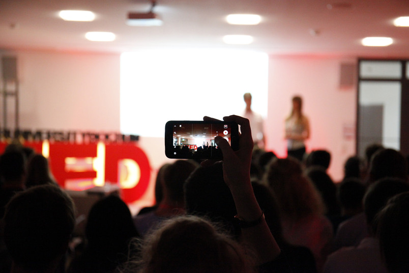 Eine Person aus dem Publikum fotografiert mit dem Smartphone eine Bühne.