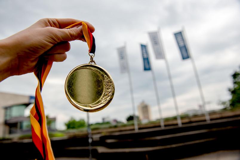 Eine Hand hält eine Goldmedaille