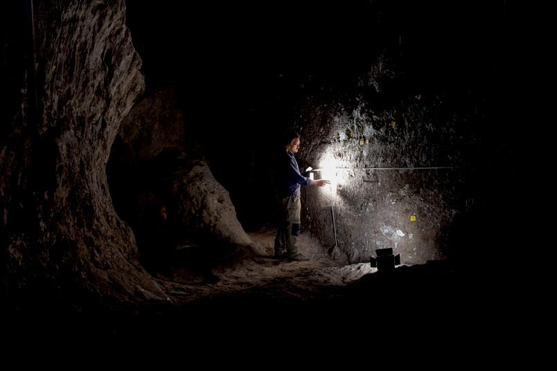 Mann in dunkler Höhle mit Taschenlampe