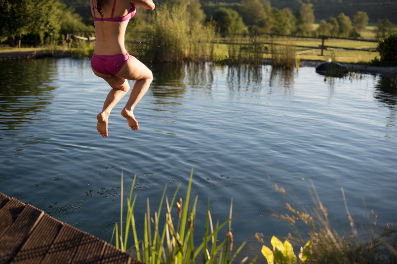 Frau springt in Fluß