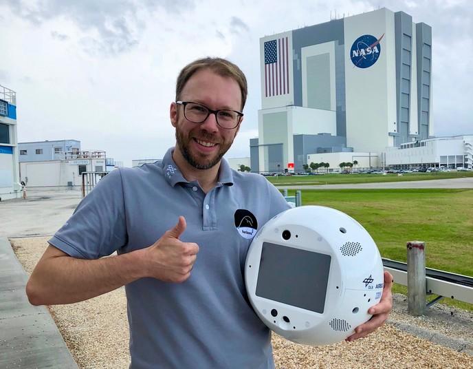 Christian Karrasch hält Roboter Cimon im Arm.