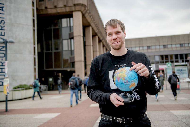 Student mit Weltkugel in der Hand.