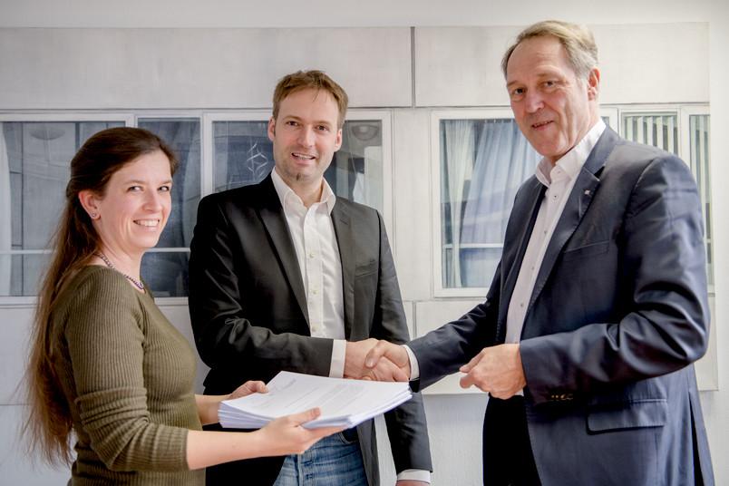 Eva und Tobias Glasmachers überreichen Rektor Axel Schölmerich die gesammelten Unterschriften (von links).
