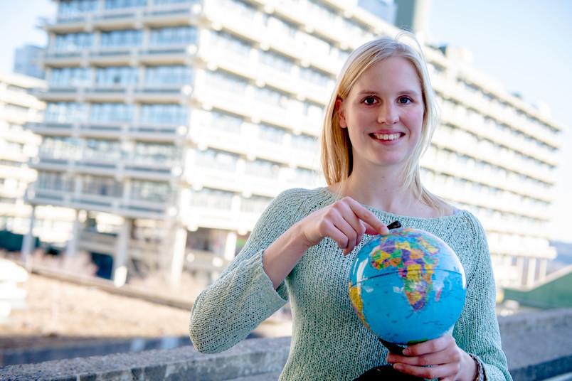 Studentin mit Globus vor RUB-Kulisse