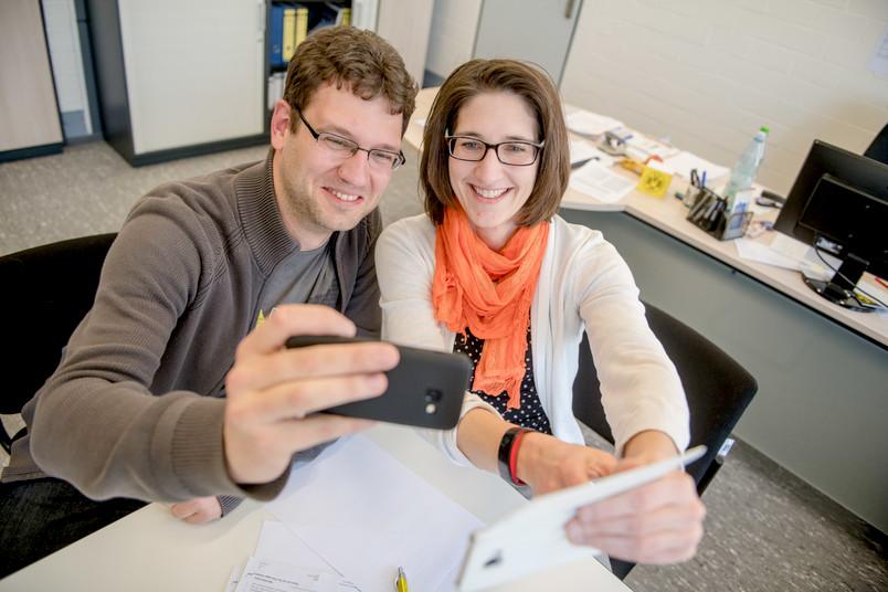 Zwei Personen machen Selfies mit zwei Handys
