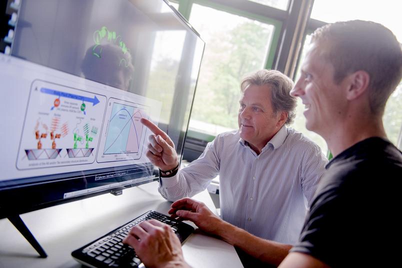 Zwei Männer vor einem Computermonitor mit Forschungsergebnissen