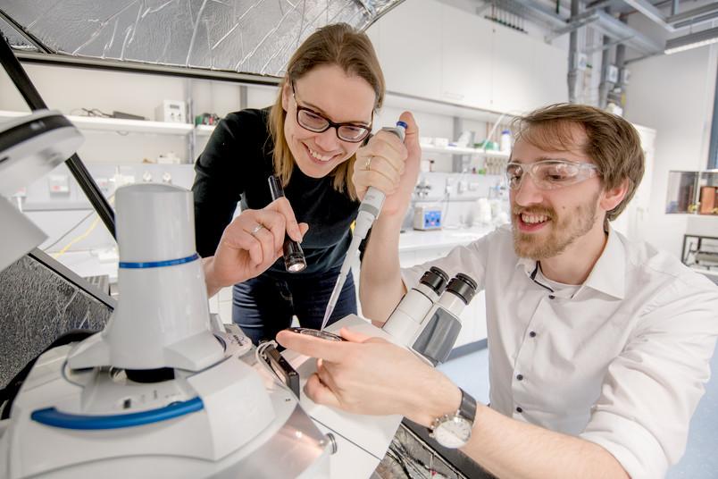 Zwei Forscher an einem Mikroskop