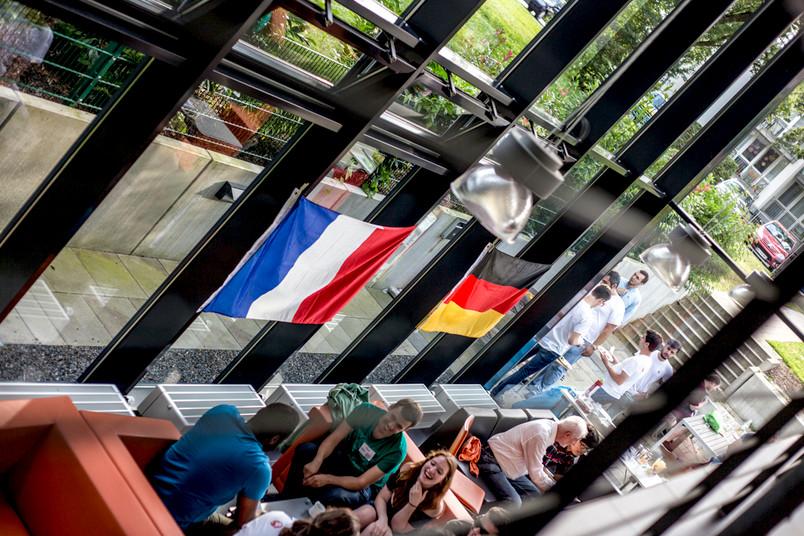 Studierende an Tischen, an der Fensterfront die deutsche und die französische Flagge