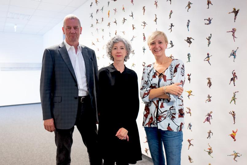 Drei Personen vor Kunstwerk