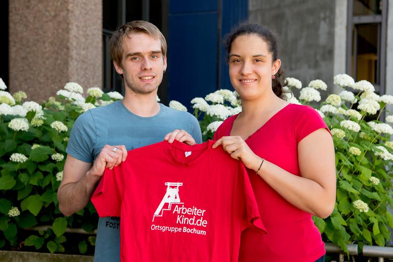 Studentin und Student halten rotes T-Shirt hoch