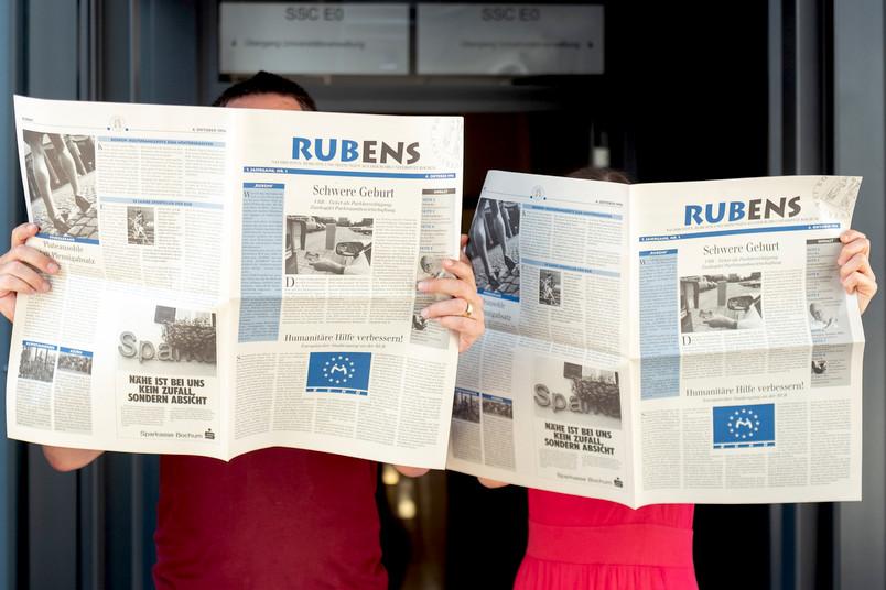 Zwei Personen halten je eine Zeitung