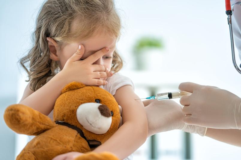 Kind mit Teddy bei Impfung