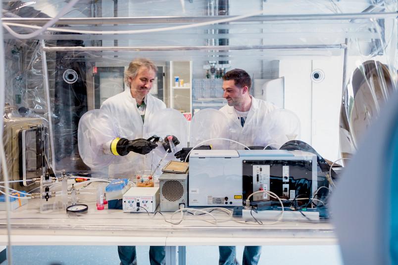 Zwei Forscher arbeiten mit einem Handschuhkasten
