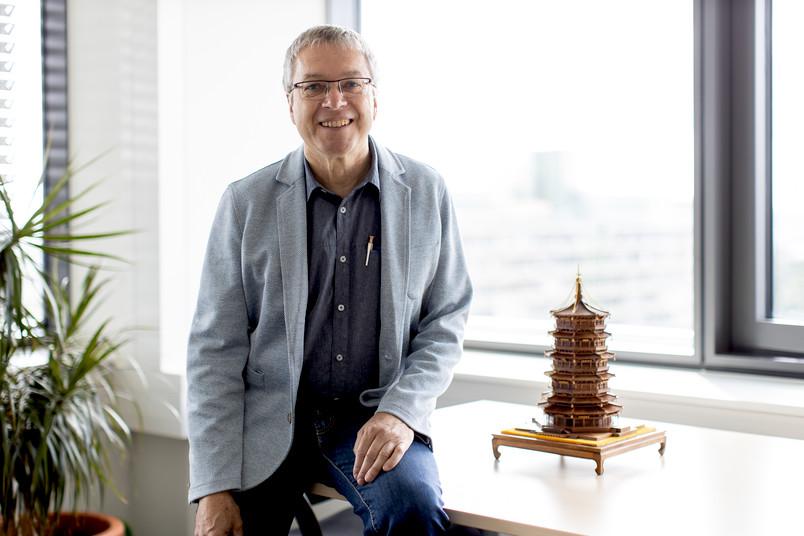 Forscher drinnen, mit chinesischem Turm auf Schreibtisch