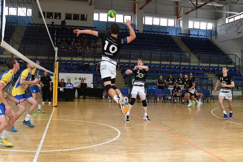 Bei einem Volleyballspiel springt ein Spieler am Netz zum Ball.