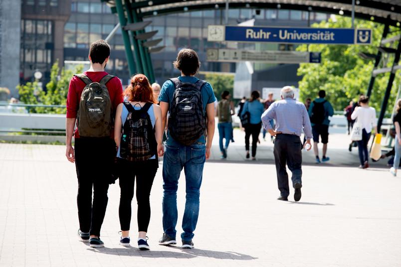 Drei Personen laufen auf der Unibrücke Richtung Haltestelle.