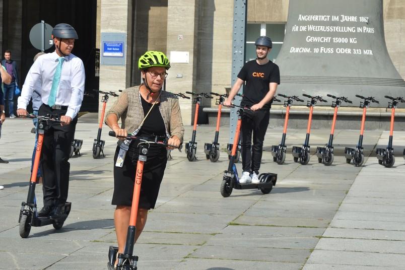 RUB-Kanzlerin Christina Reinhardt testet einen E-Tretroller vor dem Bochumer Rathaus.