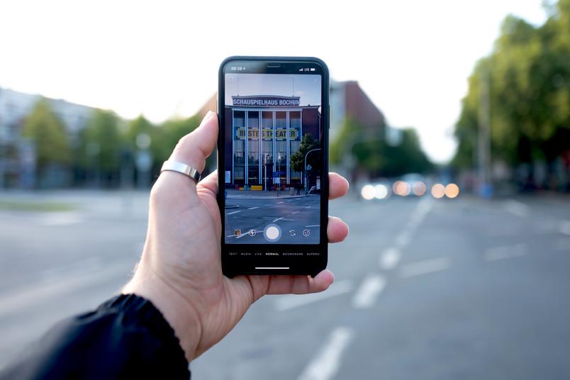 Eine Hand hält ein Smartphone, das ein Theatergebäude zeigt.