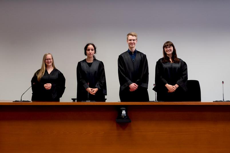 Vier Menschen stehen in Richterroben nebeneinander