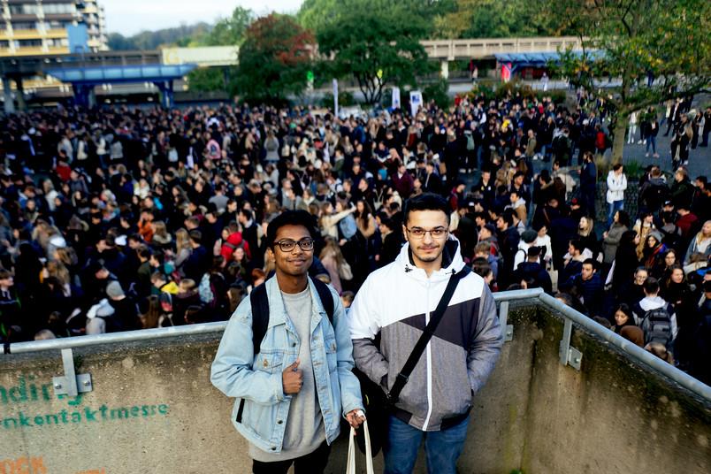 Zwei junge Männer stehen oberhalb einer Menschenmenge