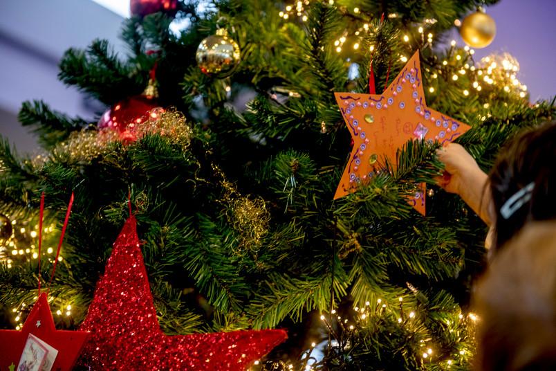 Kind hängt Wunschstern an Weihnachtsbaum
