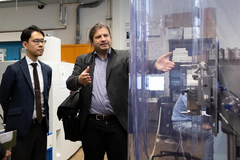 Mikito Kezuka, stellvertretender Bürgermeister von Tsukuba (links), besucht ein Labor im Arbeitsbereich von Prof. Dr. Alfred Ludwig.