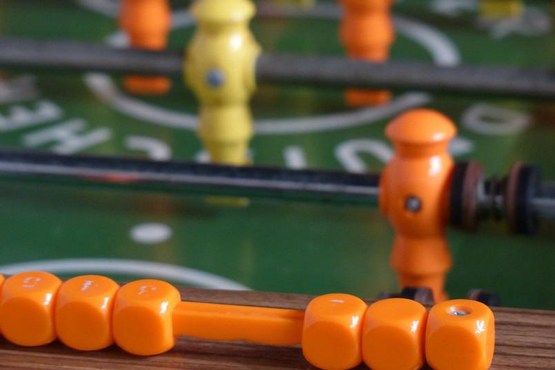 Gelbe und orangene Tischfußballfiguren in einem Kickertisch.