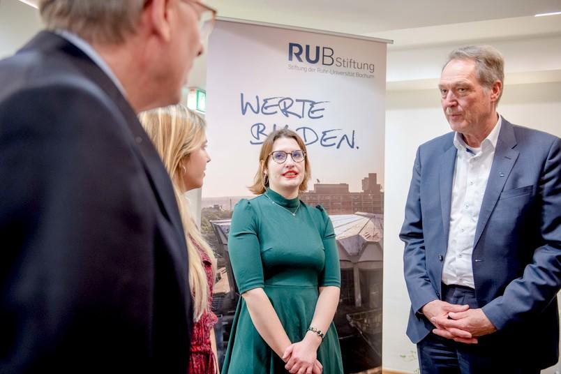 Hans-Paul Bürkner, Vorsitzender des Kuratoriums (links), und Axel Schölmerich, Vorsitzender des Vorstandes, tauschen sich mit Stipendiatinnen aus, die von der Stiftung der RUB gefördert werden.