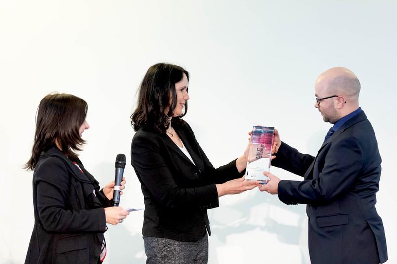 Preisverleihung mit zwei Frauen und einem Mann