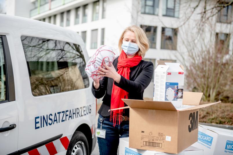Dr. Irmgard Plößl, Leiterin Einkauf und Apotheke, nimmt am St. Josef-Hospital die Schutzmaterialien aus der RUB entgegen.