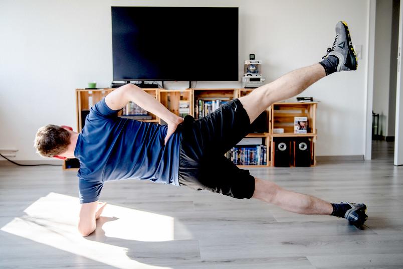 Ein Mann macht in seinem Wohnzimmer Sport.