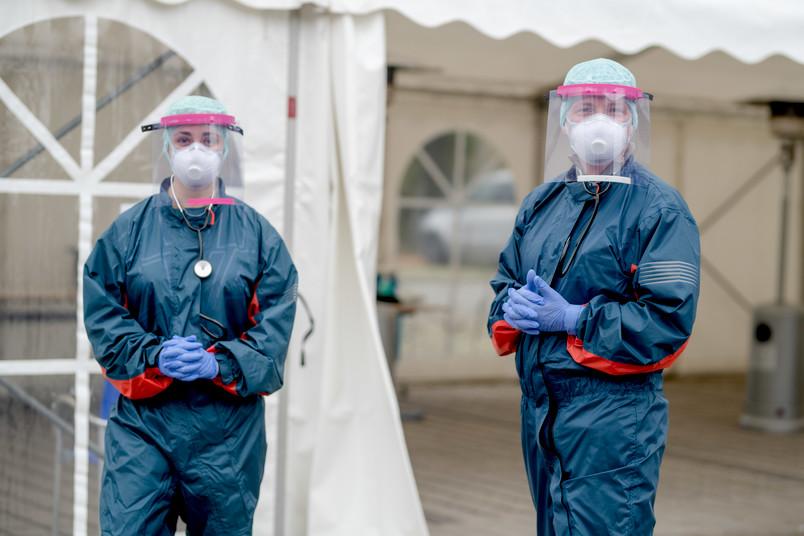 Zwei Personen in Schutzkleidung mit Gesichtsschild