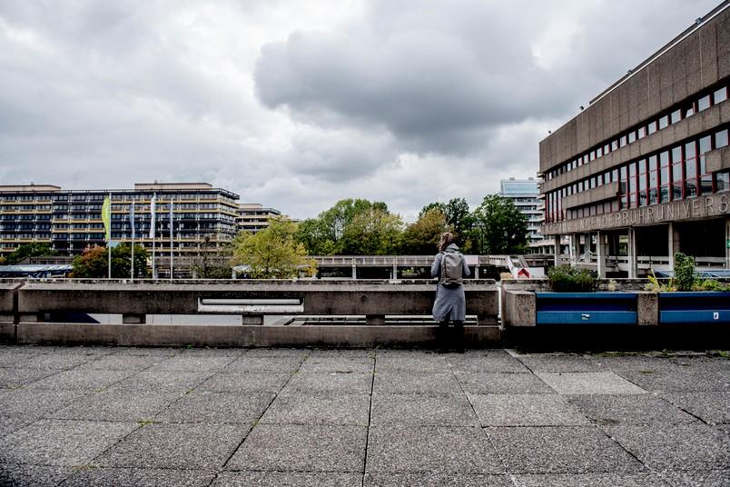 Eine Frau mit Rucksack schaut auf einem Campus in die Ferne