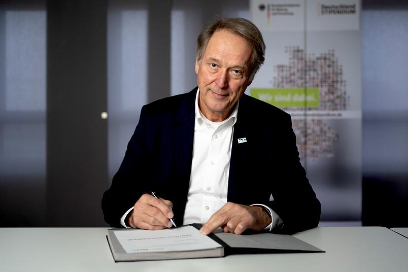 Rektor Axel Schölmerich unterschreibt