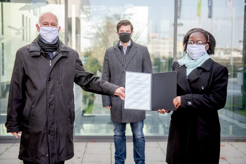 Übergabe einer Urkunde. Personen von links nach rechts: Elmar Weiler, Christoph Baer, Ngole Noumegne.