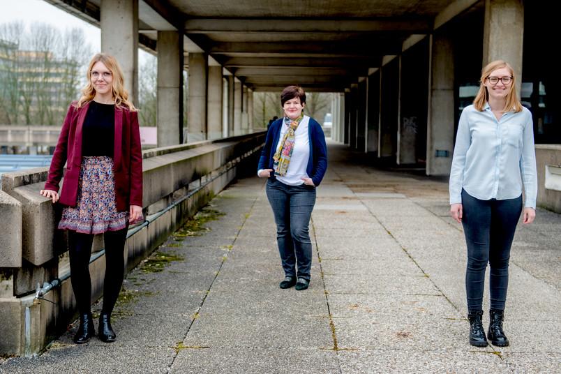 Drei Personen auf dem Campus.